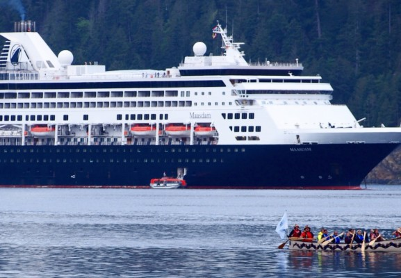 Tseshaht family paddlers greet Holland America's cruise ship Maasdam after it dropped anchor in the Alberni harbour in 2019. (Mike Youds photo)