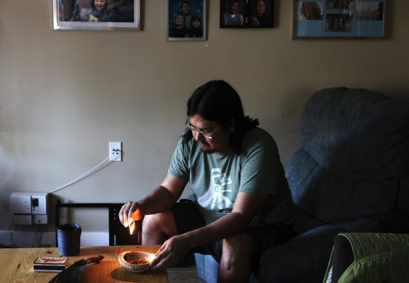 "Chris Seitcher, Tla-o-qui-aht First Nation cultural support worker, cleanses himself with sage inside his home in Ty-Histanis. ""Once I've created a safe space with myself, then I'm able to create a safe space in my house and I'm able to create a safe space with whoever comes into the house,"" said Seitcher. ""When I pray and do ceremonies, I'm able to allow protection or safety or the good energy or the good spirits to come towards me."""