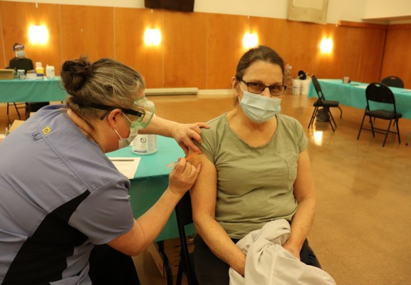 Hupacasath member Paulette Tatoosh receives her first COVID-19 shot, when NTC nurses brought Moderna doses to the House of Gathering on March 4, part of community immunization clinics being held across the province this month for on-reserve First Nations members. (Denise Titian photo)